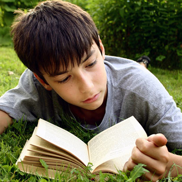 Boy laying in grass reading book