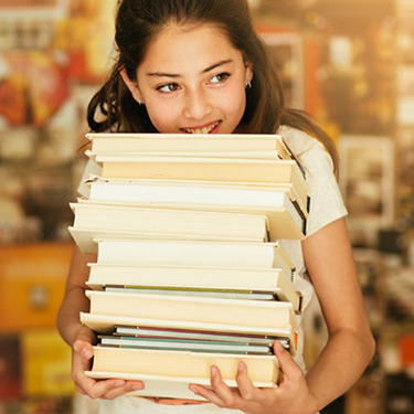 Girl holding stack of books in library